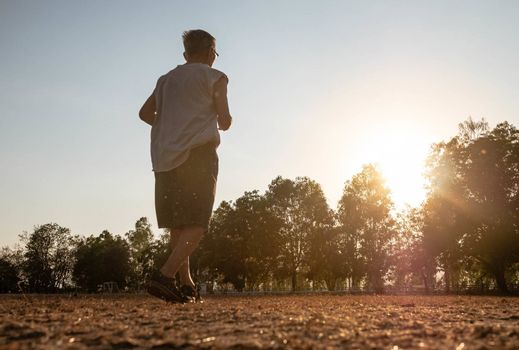 Asian senior man jogging in the park over sunset sky background. Healthy lifestyle and Healthcare concept.