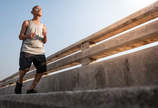 Asian senior man in sportswear jogging on bridge over sky background. Healthy lifestyle and Healthcare concept.