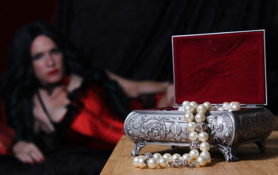Vintage Jewelry Box with Pearls, Woman in red corset in background