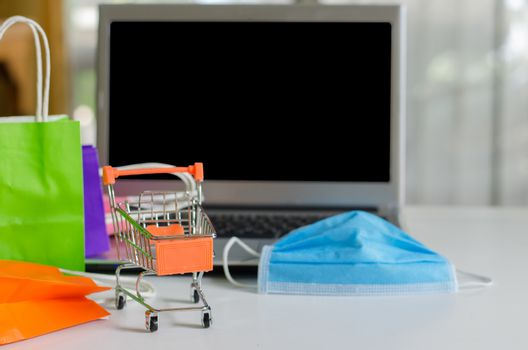 Small shopping cart on laptop with mask and  bag many colors for shopping online with home background,technology business online concept.during the Covid19 virus outbreak