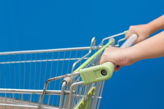 Minimalism style, Shopping cart and blue wall and human hand.