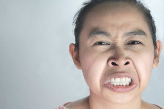 Portrait of Asian woman with hate and disgusting face in pink shirt on grey background.