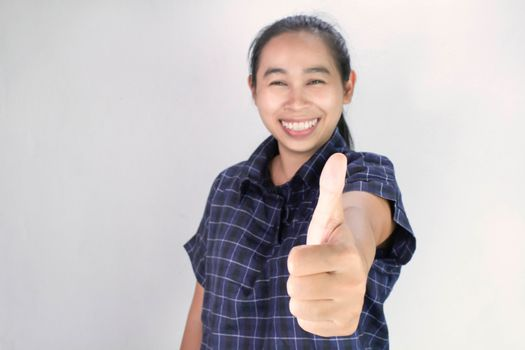 Portrait of Asian young woman in blue shirt, making outstretched hands with thumbs up sign and smiling cheerfully, showing her support. Body language and encouragement concept.