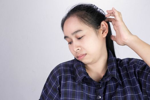 Asian young woman has itchy on her scalp isolated on grey background. Concept of scalp and hair care.