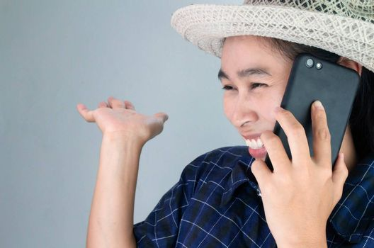 Asian young woman smiling while talking on phone in vacation day, Isolated on grey background.