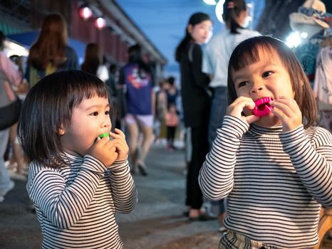 Lampang, Thailand; 5 October 2019 - Adorable Asian child girl with her sister having fun with Dracula teeth plastic toys in Kad Kong Ta Walking Street.