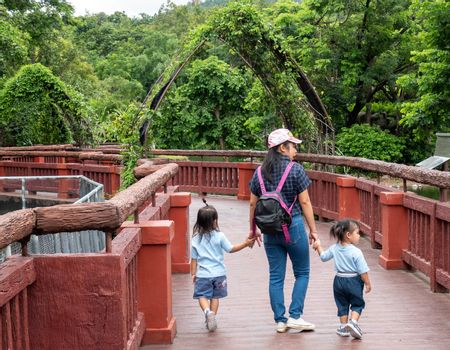 24 August 2019- Chiang Mai,Thailand ; Happy Asian family holding hands and walking together on the bridge to look animals in the Night safari.