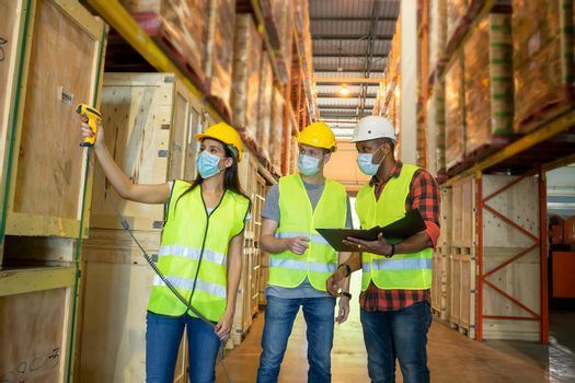 Warehouse worker scanning barcodes on boxes in a large warehouse.Concept of the center of transportation of goods.