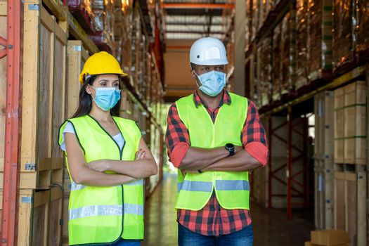 Warehouse workers wearing protective mask to Protect Against Covid-19 working at warehouse,They Work in Industry Manufacturing Factory.