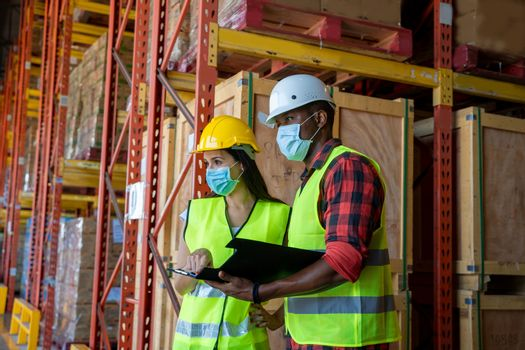 Group warehouse workers wearing protective mask to Protect Against Covid-19 working in industrial factory or warehouse.