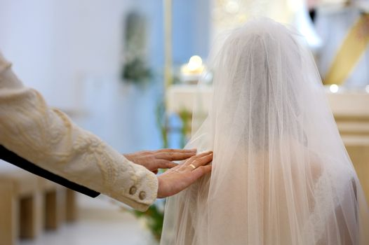 Bride's parent blessing her during wedding ceremony