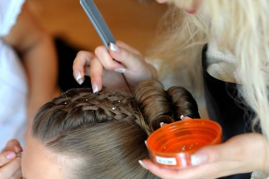 Woman's hands making a fancy hairstyle