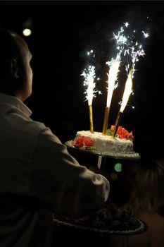 Waiter carrying white wedding cake