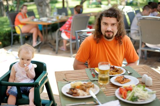 Young father and his toddler girl having a meal