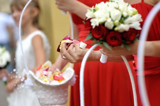 Bridesmaid holding rose petals