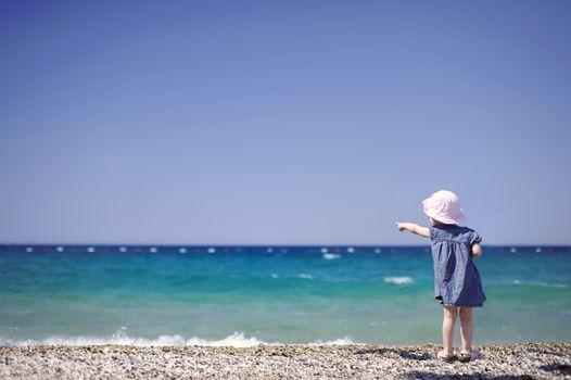 Adorable girl on a pebble beach