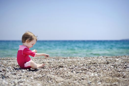 Cute girl playing on pebble beach