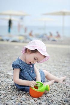 Adorable toddler girl plaiyng on a beach