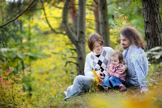 Young parents and their toddler girl having fun in autumn forest