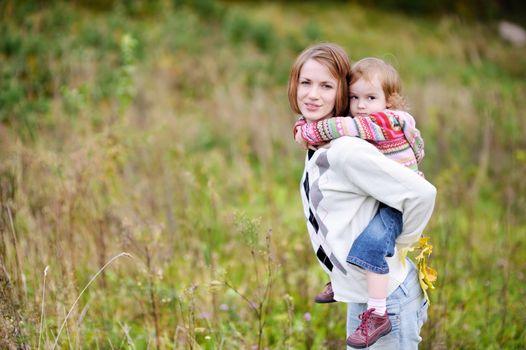 A girl having a piggyback ride on her mom
