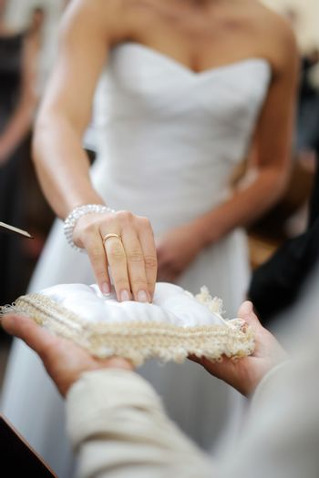 Bride taking a ring from a pillow