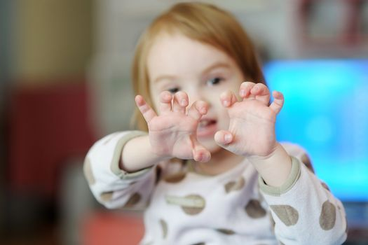 Adorable girl showing something with her fingers