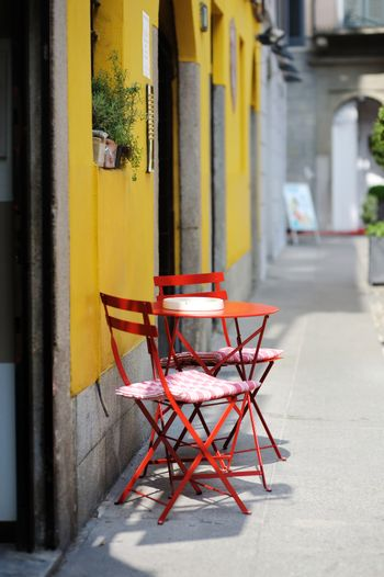 Red chairs against a yellow painted wall