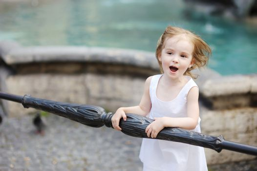 Funny child having fun by a city fountain