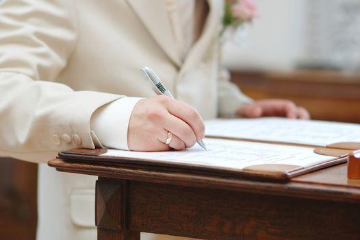 Groom signing wedding contract