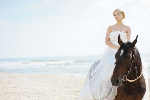 Bride on a horse by the sea
