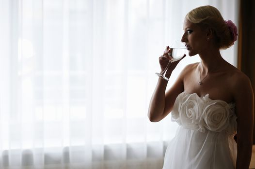 Silhouette of a bride drinking wine