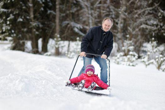 Winter fun: having a ride on a snow shovel