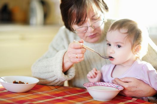 Grandmother feeding her little baby granddaughter