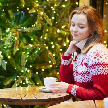 Cheerful young girl in warm red knitted holiday sweater drinking coffee or hot chocolate in cafe decorated for Christmas