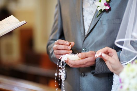 Groom is holding a wedding ring