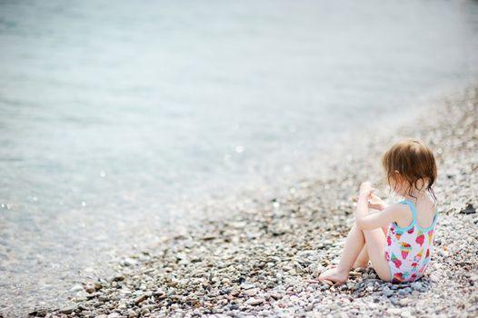Cute toddler girl on pebble beach