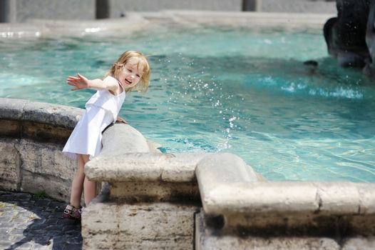 Funny child having fun by a fountain