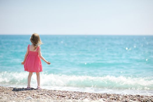 Little girl on a pebble beach