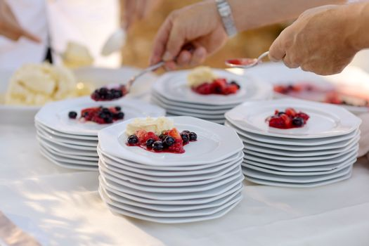 Waiter serving plates with dessert