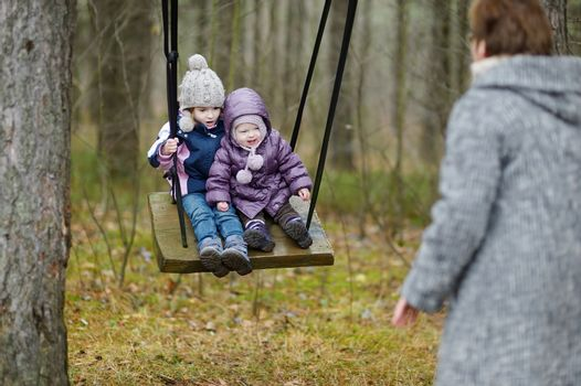 Two sisters swinging outdoors