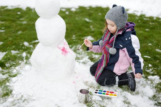 A girl painting a snowman