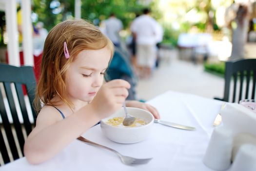 Cute little girl eating cereal