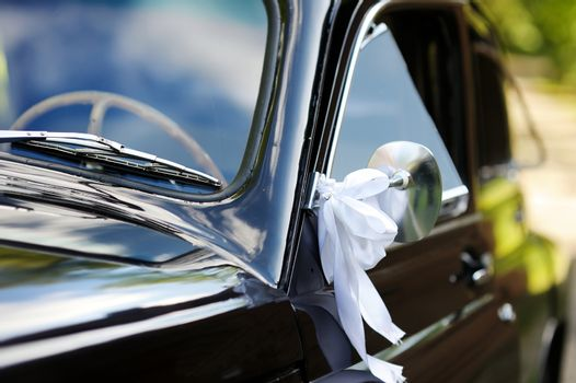 Wedding car decorated with white ribbons