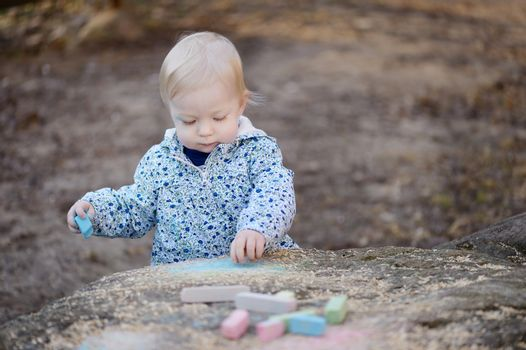 Adorable toddler girl playing with sidewalk chalk