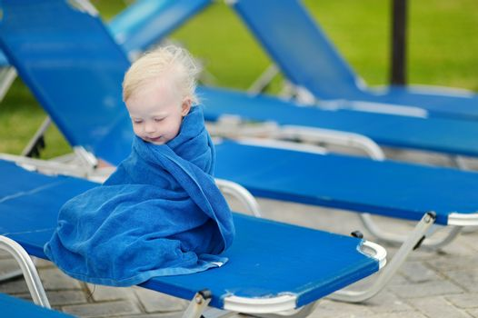 Adorable toddler girl covered with a towel