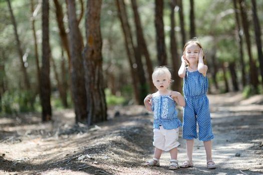 Two sisters outdoors at summer day