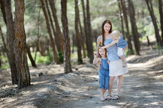Young mother and her two daughters at summer day