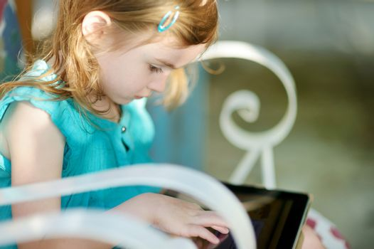 Little girl playing on a digital tablet