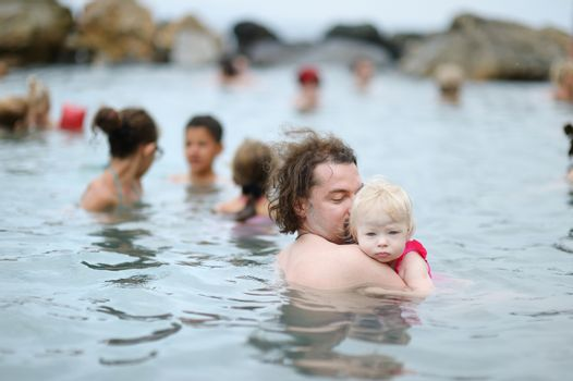 Father and his kid relaxing in hot spring on Kos island