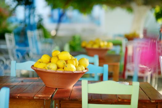 A dish of lemons in typical greek outdoor cafe